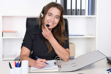 sympathetic: A young smiling businesswoman with headset is writing into a file while sitting at the desk in the office. A shelf is standing in the background. The Woman is looking to the camera. Stock Photo