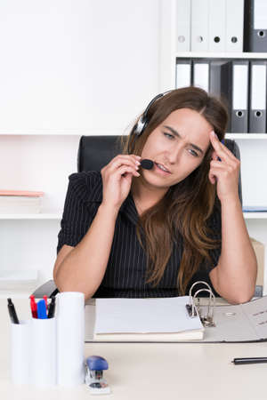 sympathetic: A young exhausted businesswoman with headset is sitting at the desk in the office. A shelf is standing in the background. The Woman is looking sideways.