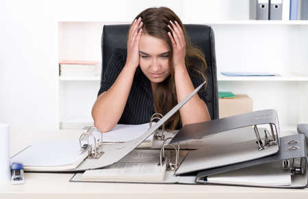 A young frustrated businesswoman is sitting in front of a pile of files at the desk in the office. A shelf is standing in the background. The woman is looking down. photo