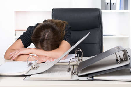 A young frustrated businesswoman is lying in front of a pile of files on the desk in the office. A shelf is standing in the background. photo