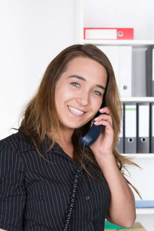 likeable: A young smiling businesswoman is phoning in the office  A shelf is standing in the background  The woman is looking to the camera