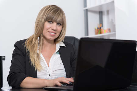 fair haired: A businesswoman is sitting behind a notebook at the desk in the office. The woman is looking to the camera.