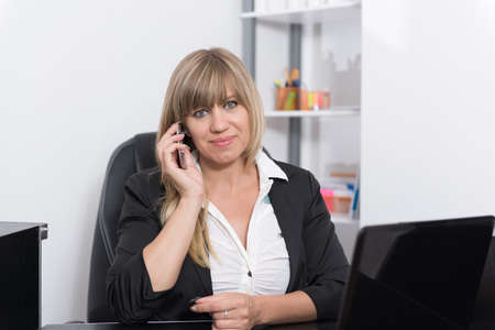 fair haired: A businesswoman is phoning with a smartphone while sitting behind a reception counter. The woman is looking to the camera.