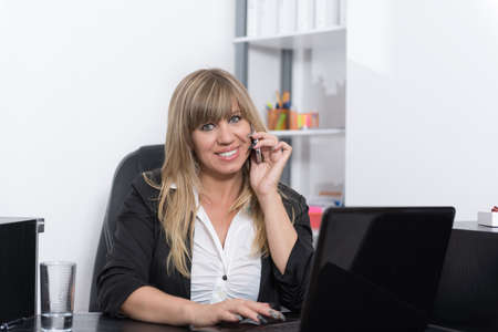 fair haired: A smiling businesswoman is phoning with a smartphone and typing at a notebook while sitting behind a reception counter. The woman is looking to the camera. Stock Photo