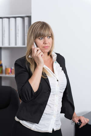 fair haired: A businesswoman is phoning with a smartphone while standing in the office. The woman is looking sideways. Stock Photo