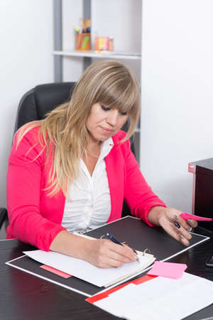 fair haired: Woman is writing into a file while sitting at the desk in the office. The woman is looking to the file.
