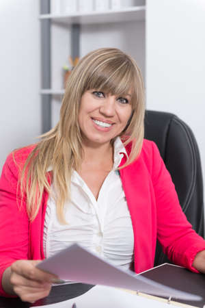 Smiling Woman is holding a document while sitting at the desk in the office. The woman is looking to the camera. photo