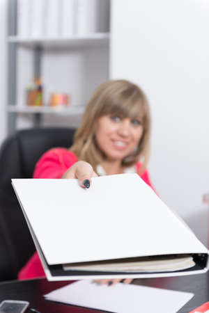 fair haired: Woman is handing over a white file in direction camera while sitting at the desk in the office. Finger is in focus, face is blurred. Stock Photo