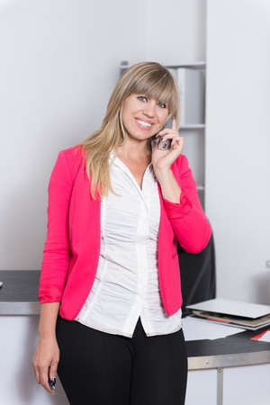 fair haired: Smiling Woman is phoning in the office. The woman is looking to the camera.