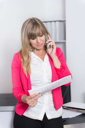 fair haired: Woman is phoning and looking at a calendar while standing in the office. The woman is looking down.