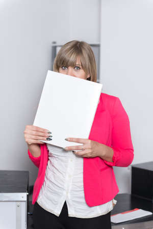 fair haired: Woman is holding a white file in front of her face while standing in the office. The woman is looking to the camera.