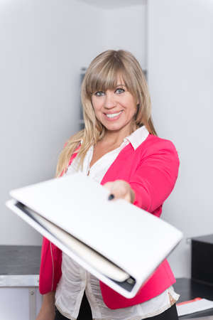 fair haired: Woman is handing over a white file in direction camera while standing in the office. Face is in focus, file is blurred.