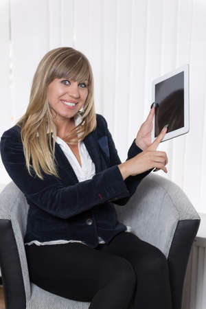 fair haired: A smiling businesswoman is pointing to a tablet with her finger while sitting on a chair. The woman is looking to the camera. Stock Photo
