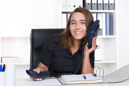 phoning: A young smiling businesswoman is holding a phone at her ear while sitting at the desk in the office. A shelf is standing in the background. The woman is looking to the camera. Stock Photo