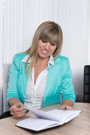 fair haired: A businesswoman is looking into an appointment calendar which is lying in front of her while she is sitting at a table in the office.