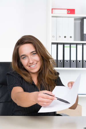 A young smiling businesswoman is pointing at a sheet of paper with a pen while sitting at the desk in the office. A shelf is standing in the background. The woman is looking to the camera. photo