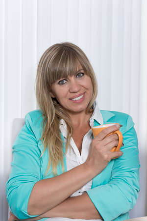 fair haired: A smiling businesswoman is holding a cup of coffee while sitting at a table in the office Stock Photo