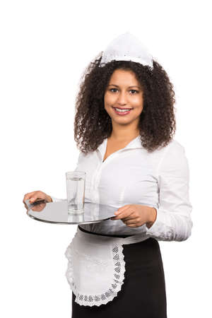 likable: Cut out image of a young smiling maid who is serving a glass of water on a tablet. The maid is wearing a service apron and cap.