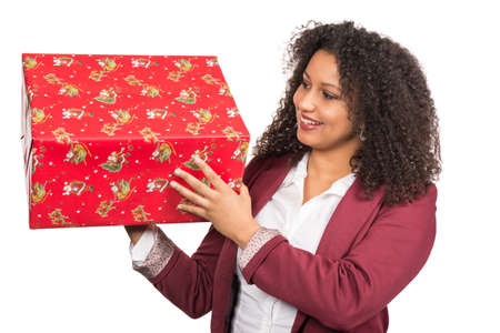 likeable: Cut out image of a young woman who is looking to a christmas gift while she is holding it. Stock Photo