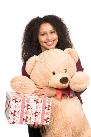 likeable: Cut out image of a young smiling woman who is holding a teddy bear and a christmas present.