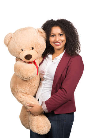 likeable: Cut out image of a young smiling woman who is holding a brown teddy bear. Stock Photo