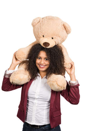 likeable: Cut out image of a young smiling woman who is carrying a brown teddy bear on her shoulders.