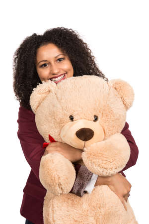 likeable: Cut out image of a young smiling woman who is hugging a brown teddy bear. Stock Photo