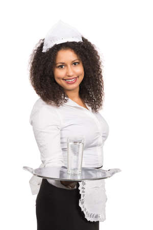 likeable: Cut out image of a young smiling serving woman with brown curly hair (afro) who is offering a glass of water on a tablet. The woman is wearing a service apron and cap. Stock Photo