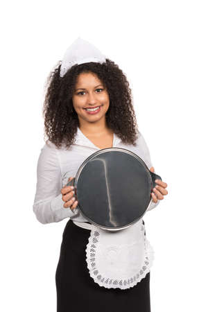 likeable: Cut out image of a young smiling maid with brown curly hair (afro) who is holding an empty tablet with both hands. The woman is wearing a service apron and cap. Stock Photo