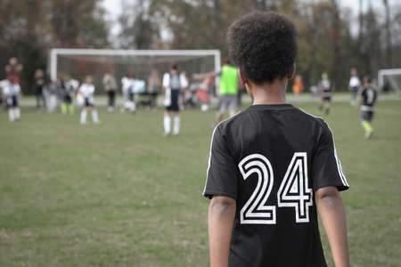 Young african american boy watching friends play football soccer game