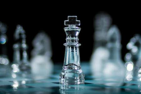 暗い背景に焦点の外にある反対のピースに囲まれたグラスキングチェスの駒