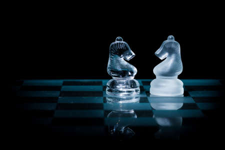 Glass Knight Chess Pieces Face Each Other on a Glass Chessboard with Black Background
