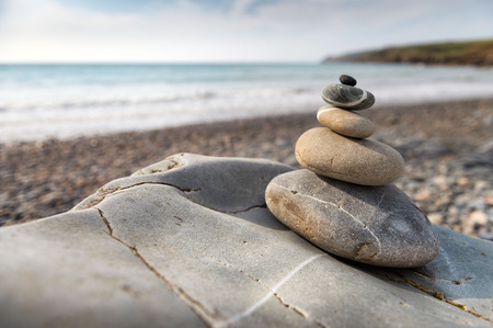 Large pebbles stacked into a tall pile on the beach, Fishguard, Wales Banco de Imagens - 74015247