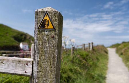 steep cliff sign: Dangerous cliff hazard warning triangle sign on coastal path. Fishguard, Wales