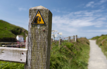 steep cliff sign: Fishguard, Wales - Dangerous cliff hazard warning triangle sign on coastal path