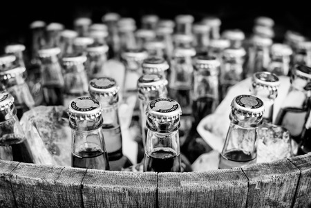 Lots of generic bottled craft beer in ice in an open barrel