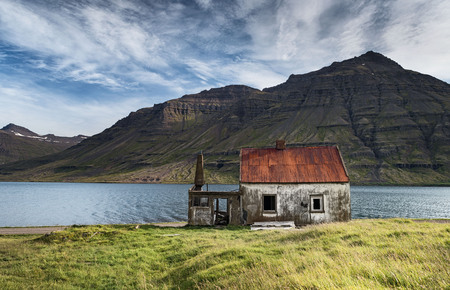 Abandoned fjordland house with a bright red roof in Seydisfjordur, Eastern Iceland