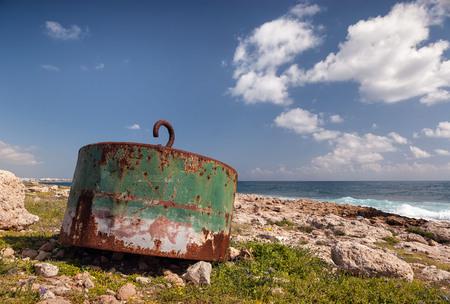 Damaged rusty ocean buoy washed ashore gives the impression of large bath plug
