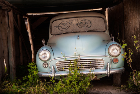 Abandoned classic car with smiling faces drawn in the dusty windscreen Stock Photo