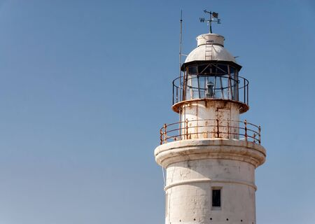 Weathered old white lighthouse closeup with weathervane pointing west