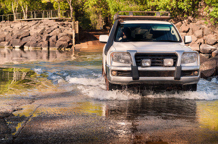 Off-road vehicle driving across a river. East Aligator Northern Territories, Australia