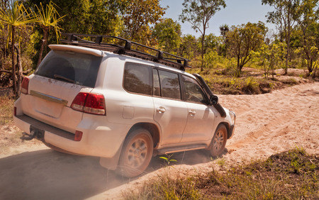 Large off-road vehicle driving through dry riverbed with wheels spinning. Northern Territories, Australia