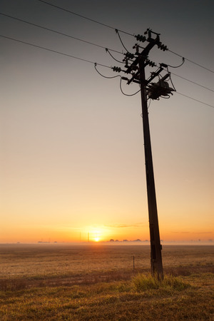 Silhouette of simple pylon and power lines at dawn. Darwin, Australia
