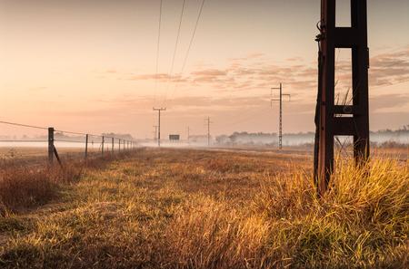 Silhouette of telphone and power lines running to the horizon at dawn. Darwin, Australia Stock Photo