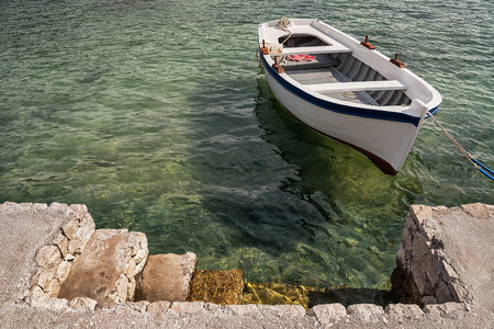 Old wooden rowing boat moored in the emerald waters of Dubrovnik harbour, Croatia Stock Photo