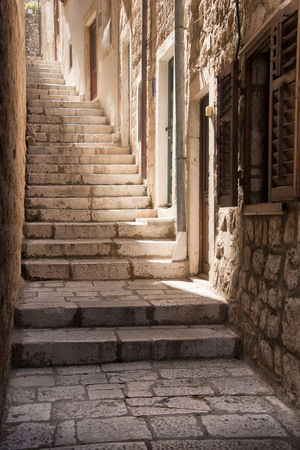 Steep steps looking up a narrow, sun-lit alleyway in Dubrovnik, Croatia Stock Photo