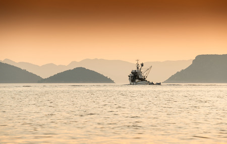 A croatian fishing boat heads out towards the islands of the Adriatic at dawn.