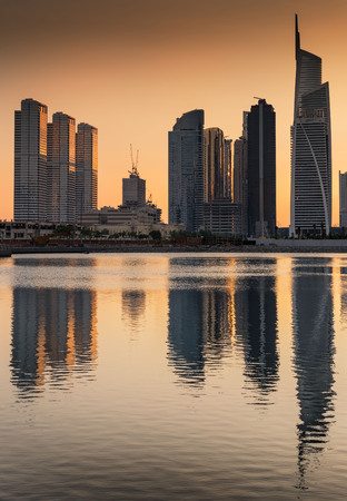 Dusk silhouettes of Jumeirah lakes towers reflected in water, Dubai, United Arab Emirates Stock Photo