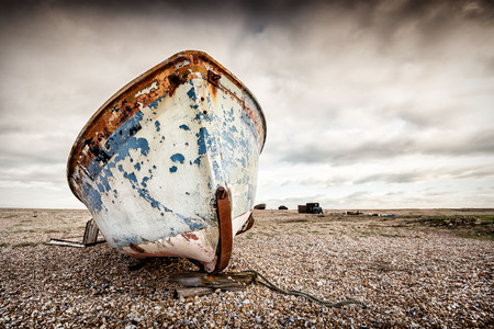 Single abandoned old fishing boat on a pebble beach. Dungeness, England