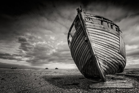 Single abandoned old fishing boat on a pebble beach in monochrome. Dungeness, England
